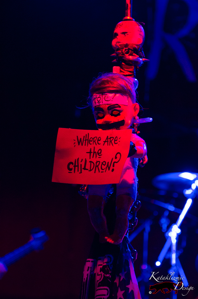 "Creepy baby doll holding a sign reading ""Where are the children?"" - Photography: Katherine Amy Vega"